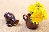 stock photo of vase flowers  - Bouquet of yellow fresh flowers of dandelion in brown vase and overturned vase in background lying on jute canvas - JPG