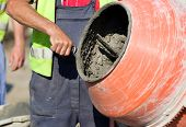 pic of mixer  - Construction worker mixing ingredients in the concrete mixer at building site - JPG