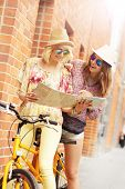 stock photo of tandem bicycle  - A picture of two girl friends using a map and riding a tandem bicycle in the city - JPG