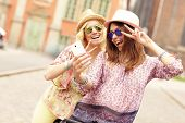 foto of tandem bicycle  - A picture of two girl friends using smartphone while riding tandem bicycle - JPG