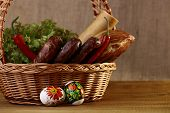 stock photo of home-made bread  - Meat home made tasty sausages lattuce bread rolls red pepper and easter eggs in basket horizontal picture - JPG