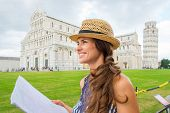 picture of piazza  - A smiling female tourist holding a map is looking into the distance - JPG