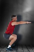 picture of squatting  - Fit man doing a squat against dark grey room - JPG