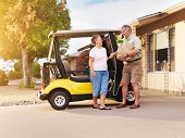 stock photo of grocery cart  - active senior couple coming home with groceries on golf cart - JPG