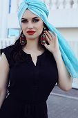 stock photo of turban  - fashion outdoor photo of beautiful sensual woman with long dark hair wearing elegant black dress and silk turban on head - JPG