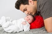 stock photo of cuddle  - Loving father cuddling his new born baby - JPG