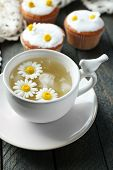 picture of chamomile  - Cup of chamomile tea with chamomile flowers and tasty muffins  on color wooden background - JPG