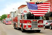 image of fire truck  - A group of fire trucks with American flags on them drive down the road in a small town American Parade during a festival event - JPG