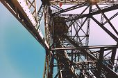 pic of ropeway  - Metal designs inside of a tower of a ropeway in Barcelona against the sky - JPG