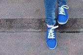 foto of street-walker  - Female feet in gumshoes on  stone stairs - JPG