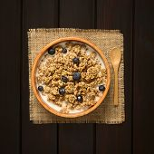 stock photo of cereal bowl  - Dried berry and oatmeal breakfast cereal with fresh blueberries and milk in wooden bowl photographed overhead on dark wood with natural light - JPG