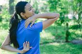 pic of pain-tree  - Closeup portrait young woman in pigtail and blue shirt feeling severe tormenting agony from back neck pain isolated green trees background outside outdoors - JPG