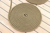image of roping  - Old nautical thick rope wrapped in spiral lying on weathered deck of yacht circle of thick rope - JPG