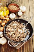 stock photo of champignons  - Buckwheat porridge with champignons in a metal pot on the table - JPG