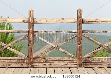 Summer landscape with green hills and wooden fence. Fence with pine trees in the background.