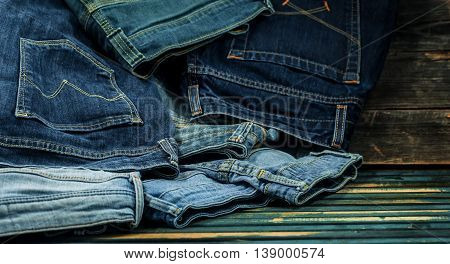 Bunch Of Jeans On A Wooden Background Strewn, Fashionable Clothes