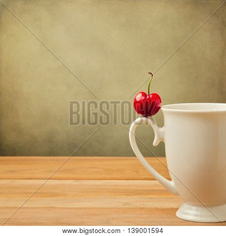 Single cherry on cup handle over grunge background
