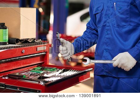 Cropped image of mechanic choosing tools from the box