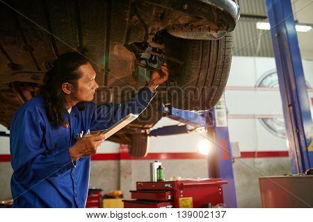 Experienced mechanic checking car wheel in garage