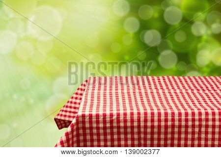 Empty table with red checked tablecloth over green bokeh background. Perfect for product montage display