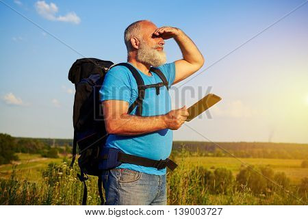 Handsome bearded aged tourist with rucksack is standing in the field and looking into the distance his hand covering eyes from bright sunset sun