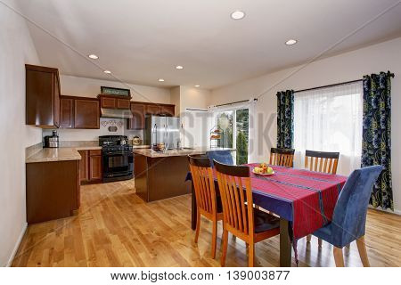 Bright Kitchen And Dining Room Interior With Colorful Curtains And Hardwood Floor.