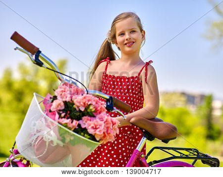 Portrait of girl on bicycle . Child girl wearing red polka dots dress rides bicycle with flowers basket. Blu sky on background summer park.