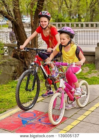 Children girls wearing bicycle helmet with rucksack ciclyng bicycle. Girls children cycling on yellow bike lane. Bike share program save money and time. City trip.