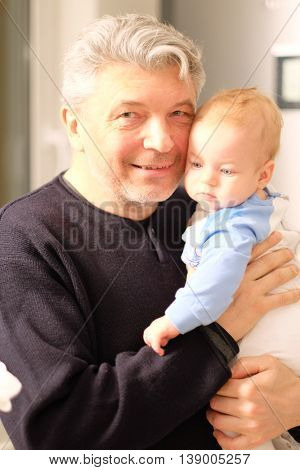 Newborn baby with his grandfather. Shallow depth of field.