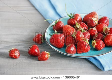Ceramic plate with strawberries at old wooden table in daylight. Close up high resolution product. Harvest Concept
