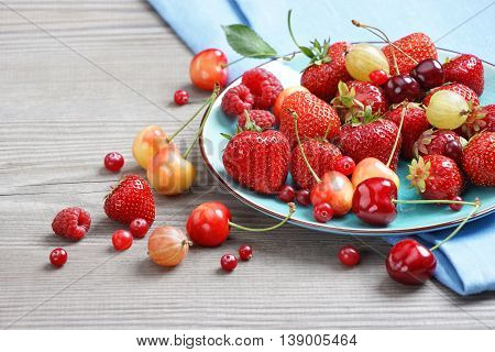 Ceramic plate with mixed berries at old wooden table. Close up high resolution product. Harvest Concept