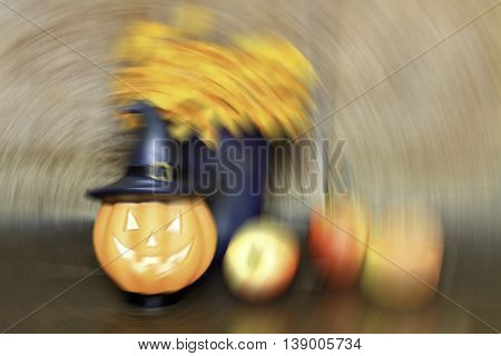 halloween set de-focused pumpkin doll and apple on wooden background spin blur