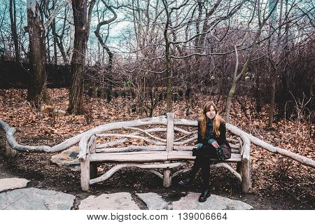 Girl Sitting On A Bench At The Central Park In Manhattan, New York City