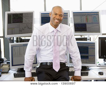 Portrait Of Stock Trader In Front Of Computer Monitors