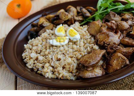 Barley porridge fried mushrooms and duck liver boiled quail eggs tomatoes arugula - healthy food.