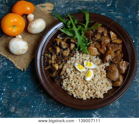Barley porridge fried mushrooms and duck liver boiled quail eggs tomatoes arugula - healthy food. The top view