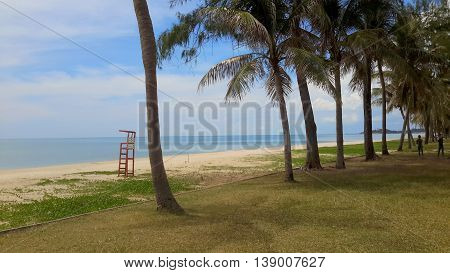 row of coconut trees along the shore, with a red lifeguard stand on the beach sand, two statues of children in the far background, Songkhla, Thailand