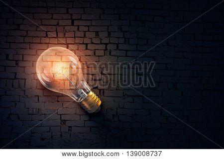 Glowing bulb on brick surface . Mixed media