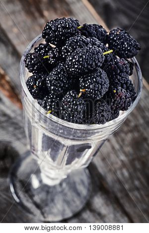 Sweet and sour fresh organic ripe mulberries in wine glass on wooden background. Black berries Dark style photo.