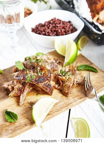 Sliced cuban style slow roasted pork shoulder in mojo marinade and sauce on wood board with limes and mint near it . White wood background with brown rice bowl and big roasted shoulder in pan on back