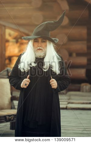 Old man wizard with long grey hair beard in black costume and hat for Halloween standing near wooden chair on log house background