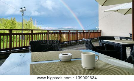 rainbow and cup of coffe on table in the mountains