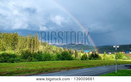 rainbow above road and village at the summer in mountains landscape