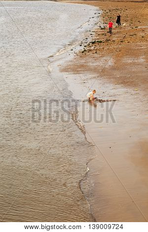 WHITBY ENGLAND - JULY 16: Various people on the beach young boy playing in the edge of the sea. In Whitby North Yorkshire England. On 16th July 2016.