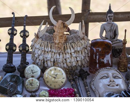 INLE LAKE MYANMAR - JANUARY 12 2016: Hat - crown of the teeth of animals and others hand-made souvenirs on the counter of the market. Inle Lake. Myanmar