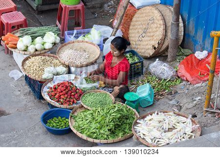 YANGON MYANMAR - JANUARY 09 2016: Unidentified woman sell vegetables and fruits on the street food market in the city center
