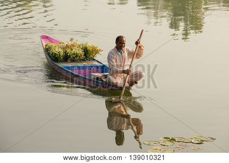 SRINAGAR INDIA - JULY 07 2015 : Lifestyle in Dal lake people use Shikara a small boat for transportation in the lake of Srinagar India. Local florist with bouquets for sale on a boat tour