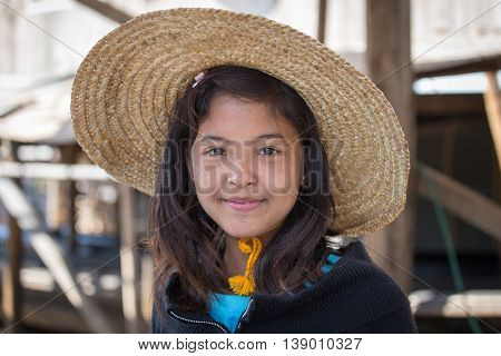 INLE LAKE MYANMAR - JANUARY 12 2016: Portrait burmese girl a straw hat in local market. Inle lake Myanmar Burma