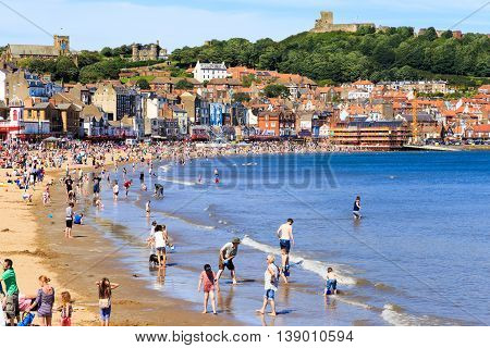 SCARBOROUGH ENGLAND - JULY 16: Lots of people enjoying Scarborough beach on a hot summer day. In Scarborough North Yorkshire England. On 16th July 2016.