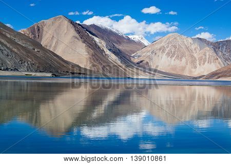 Sunny day at Pangong Lake and Himalayan mountain. Pangong Lake is an endorheic lake in the Himalayas situated at a height of about 4350 m in Ladakh India. It is 134 km long from India to Tibet